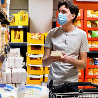 Young man with a protective medical mask looking for sugar at the supermarket's shelves near the cart. Corona Virus idea - Starpik Stock