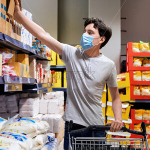 Young man with a protective medical mask taking sugar from the supermarket's shelves near the cart. Corona Virus idea - Starpik Stock
