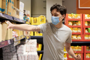 Young man with a protective medical mask taking whipped cream from the supermarket's shelves. Corona Virus idea - Starpik Stock