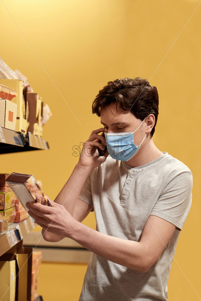 Young man with a protective medical mask talking on the phone while looking at the snacks from the shelves in a supermarket. Corona Virus idea - Starpik Stock