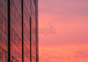 the colorful sky during sunset is reflected in the windows of the building, Bucharest, Romania - Starpik Stock