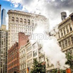 NEW YORK, USA – SEPTEMBER 19, 2019: Block of flats with skyscrapers and Flatiron Building on the background. Vibrant colors - Starpik Stock
