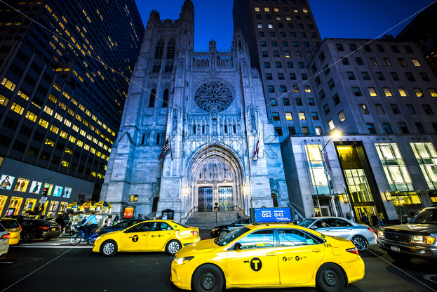 NEW YORK, USA – SEPTEMBER 19, 2019: Saint Thomas Church at night with cars on the foreground. Vibrant colors - Starpik Stock