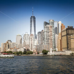View of Manhattan from the water, cruise ship on the foreground, multiple high buildings in New York, USA. Vibrant colors - Starpik Stock