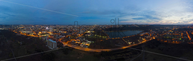 Aerial drone panoramic view of Chisinau cityscape with lights at night, Moldova - Starpik Stock