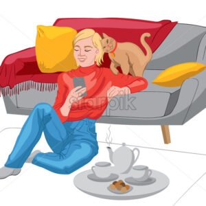 Happy woman dressed in red sweater and jeans looking in her phone while sitting on the floor and leaning on the sofa. Teapot, tea cups and biscuits on a plate. Cat with red collar playing. Vector - Starpik Stock