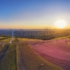 Panorama of wind turbine in a windfarm on hills in Moldova at sunset, aerial drone view with glowing sun - Starpik Stock