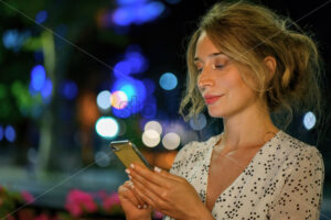 Woman with phone night portrait city lights bokeh. White dress lovely evening scene - Starpik Stock