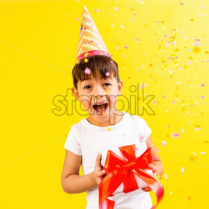 A caucasian child in holiday cap is happy with a gift box, confetti. Blue background. Holiday concept. Front view - Starpik Stock