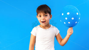 A caucasian child is happy with a balloon with white circles. Blue background. Holiday concept. Front view - Starpik Stock