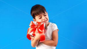 A caucasian child is pleased with a gift box. Blue background. Holiday concept. Front view - Starpik Stock
