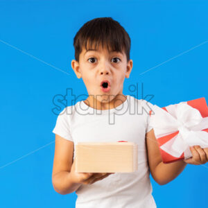 A caucasian child is surprised with a gift box. Blue background. Holiday concept. Front view - Starpik Stock