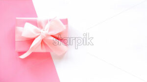 A gift box with a tape on two-color background. Pink and white colors. Holiday concept. Top view - Starpik Stock