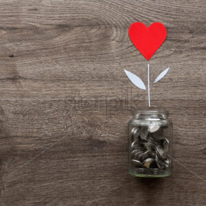 A glass can with metal coins and a flower with red heart growing up in it. Wooden background. Top view - Starpik Stock