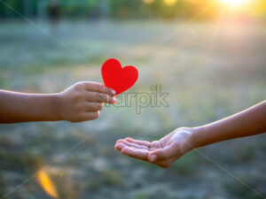 A kid is giving a man a red heart, setting sun. Love concept - Starpik Stock