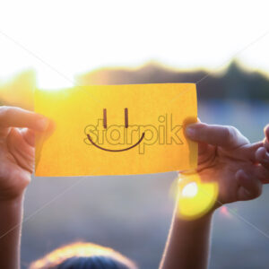 A kid is holding a paper with positive face on it, setting sun - Starpik Stock