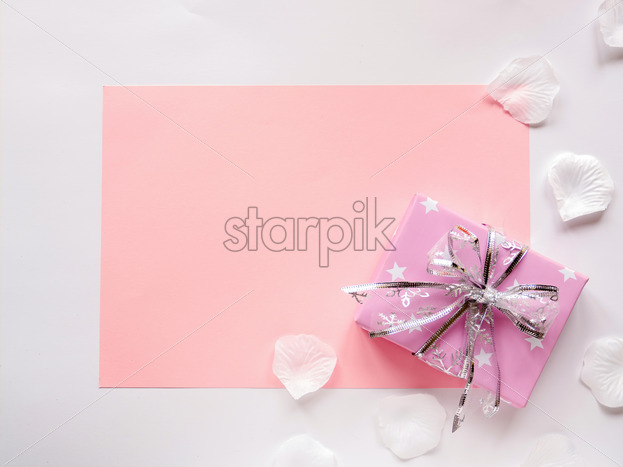A pink paper sheet and gift box on white background, petals around. Top view - Starpik Stock