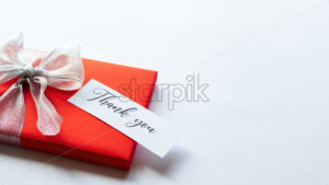A red gift box with grey tape and a note with message. White background. Holiday concept - Starpik Stock