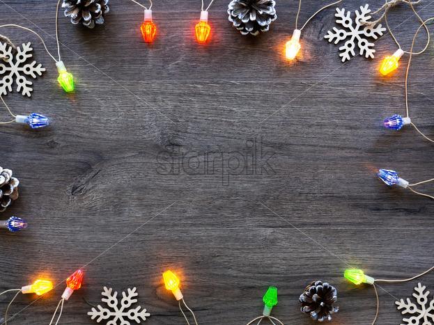 Christmas decorations, fir cones and illumination. Wooden background. Holiday concept. Top view - Starpik Stock