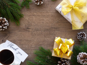 Christmas tree branches with firs cones and gift box with cup of coffee, note with a message. Wooden background. Holiday concept. Top view - Starpik Stock