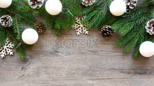 Christmas tree branches with firs cones and holiday decorations. Wooden background. Holiday concept. Top view - Starpik Stock