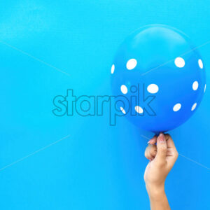 Female hand holds a balloon with white circles on blue background. Holiday concept. Top view - Starpik Stock