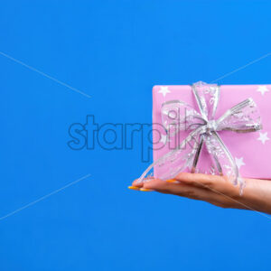 Female hand holds a gift box on blue background. Holiday concept. Front view - Starpik Stock