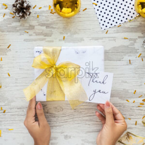 Female hand holds a gift box with golden tape, note with message, Christmas decoration around. Wooden background. Holiday concept. - Starpik Stock