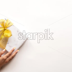 Female hand holds a gift box with golden tape on white background. Holiday concept. - Starpik Stock