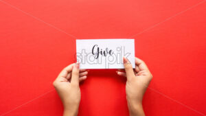 Female hand holds a note with message. Red background. Front view - Starpik Stock