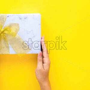 Female hands hold a gift box on yellow background. Holiday concept. Top view - Starpik Stock
