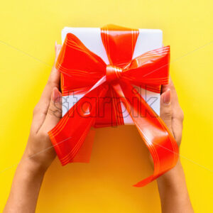 Female hands hold a gift box, tapes around on yellow background. Holiday concept. Top view - Starpik Stock