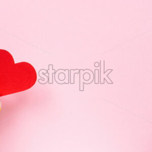 Female hands hold a red heart on pink background. Holiday concept. Front view - Starpik Stock