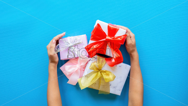 Female hands hold few gift boxes on blue background. Holiday concept. Top view - Starpik Stock