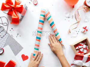 Female hands on table with things for preparing gifts, gift boxes, tapes, stationery. Holiday concept. Top view - Starpik Stock