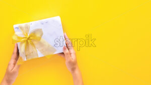 Female hold holds a gift box on yellow background. Holiday concept. Top view - Starpik Stock