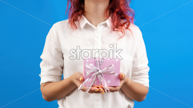 Female holds a gift box on blue background. Holiday concept. Front view - Starpik Stock