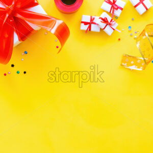 Few gift boxes with red tape, decoration around on yellow background. Holiday concept. Top view - Starpik Stock