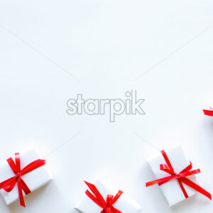 Few gift boxes with red tape on white background. Holiday concept. Top view - Starpik Stock