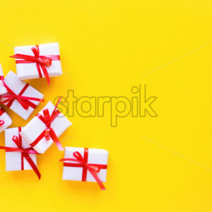 Few gift boxes with red tape on yellow background. Holiday concept. Top view - Starpik Stock
