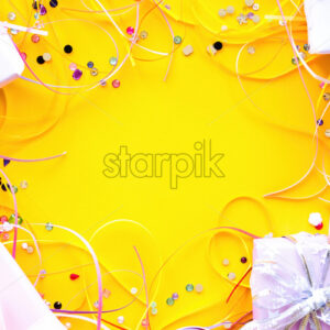 Few gift boxes with tapes and decoration around on yellow background. Holiday concept. Top view - Starpik Stock