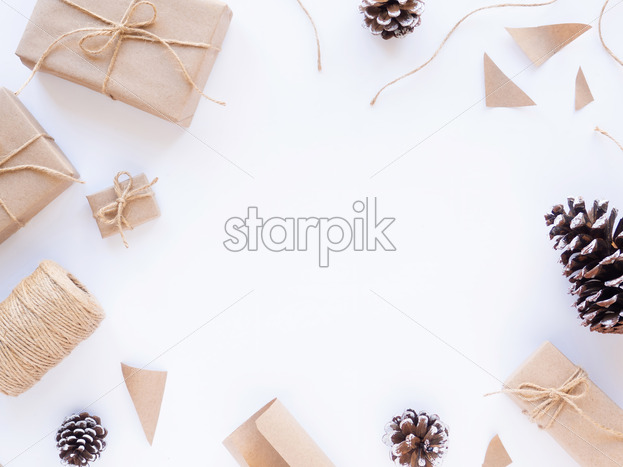 Gift boxes, bits of papers, fir cones, twine. White background. Holiday concept. Top view - Starpik Stock