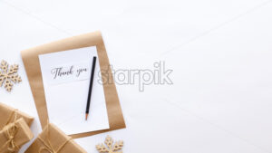 Gift boxes, decoration, notebook with a message and a pencil. White background. Holiday concept. Top view - Starpik Stock