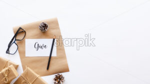 Gift boxes, fir cones, note with a message and a pencil, glasses. White background. Holiday concept. Top view - Starpik Stock