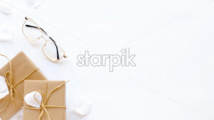 Gift boxes, glasses, rose petals. White background. Holiday concept. Top view - Starpik Stock