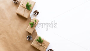 Gift boxes with Christmas tree branches and fir cones on two-color background. Pink and white colors. Holiday concept. Top view - Starpik Stock