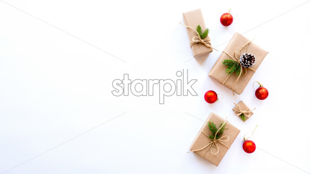 Gift boxes with Christmas tree branches and fir cones on white background. Holiday concept. Top view - Starpik Stock