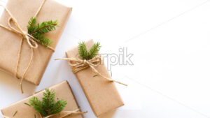 Gift boxes with attached Christmas tree branch. White background. Holiday concept. Top view - Starpik Stock