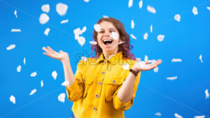 Happy smiling caucasian woman with confetti around in the air, blue background. Holiday concept. Front view - Starpik Stock