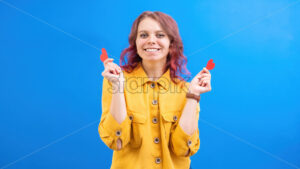 Happy smiling caucasian woman with two red hearts in hands, blue background. Love concept. Front view - Starpik Stock